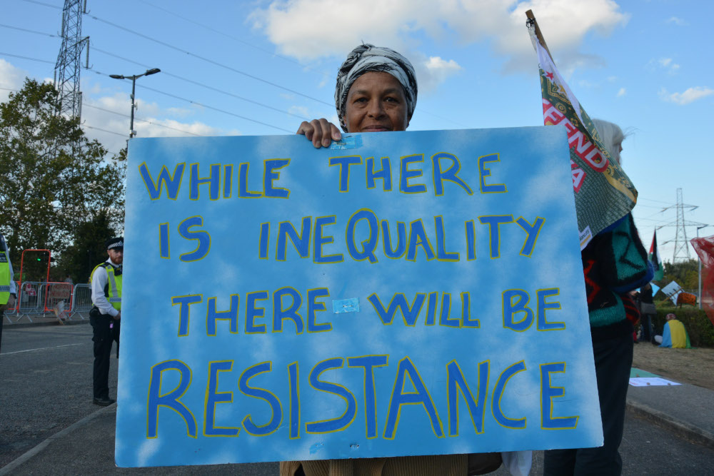 Person holds big placard saying Where there is inequality there will be resistance